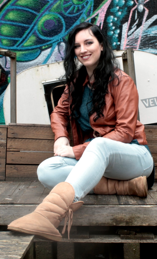 author m evan macgriogair on a wooden bench in front of a graffiti wall. author is white and has long, wavy black hair and is wearing pale jeans, a red-brown pleather jacket, and a teal shirt that matches the graffiti. and terrible fake uggs.