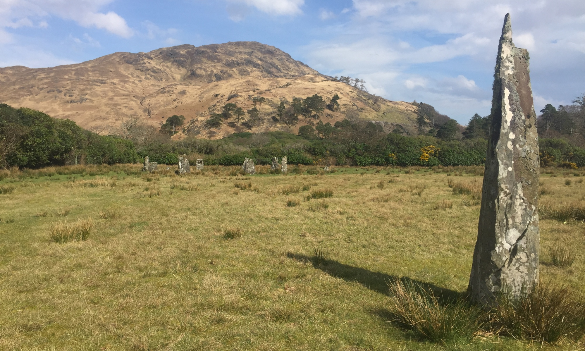 standing stones near loch buie, isle of mull. one stone stands in the foreground with a ring in the distance and a hill rising behind them on a bright sunny day.